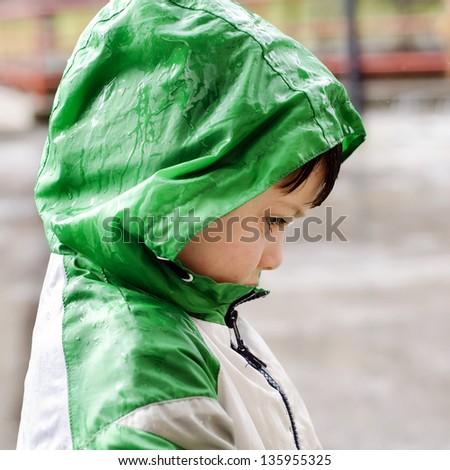 Child in waterproof jacket in the rain, profile portrait. - stock photo