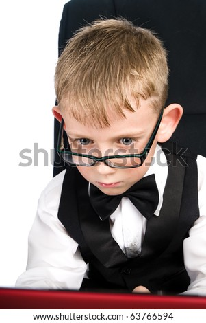 Child in white shirt and bow tie looks in laptop - stock photo