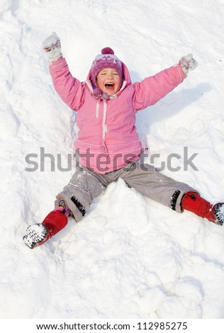 Child in winter. Girl rolling down the hills - stock photo