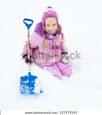 Child in winter. Happy girl digging a snow shovel - stock photo