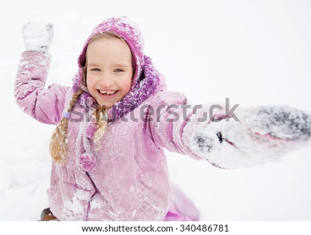 Child in winter. Happy girl on snow. Playing snowballs - stock photo