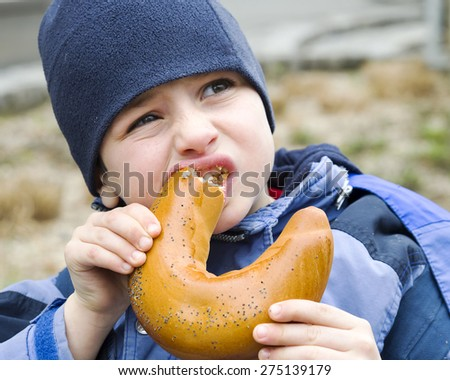 Child in winter hat eating chocolate croissant bun roll at street or park, aid or poverty concept. - stock photo