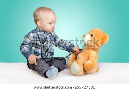 Child is a doctor. Playing with teddy bear - stock photo