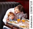 Child is a picky eater in restaurant and father tries to feed it - stock photo