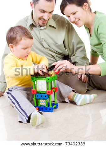 Child is building a house with patents (wit focus on child) - stock photo