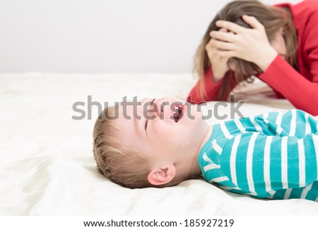child is crying whild mother is tired, difficult parenting - stock photo