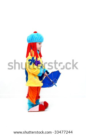 Child is dressed as a clown complete with red yarn hair and hat.  He is wearing over sized shoes and carrying a tiny umbrella. - stock photo