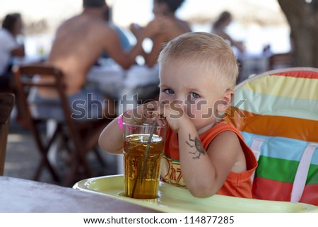 Child is drinking apple juice in a cafe - stock photo