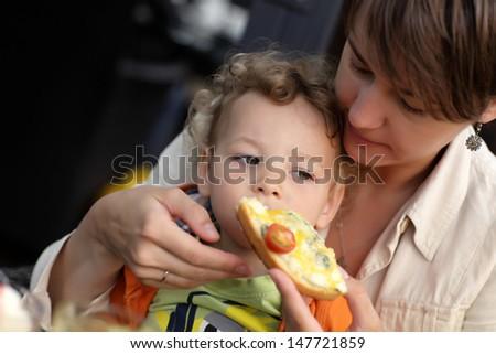 Child is eating bruschetta in a restaurant - stock photo