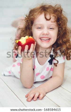 Child is eating red apple - stock photo