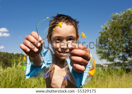 child is holding field flowers on warm summer day - stock photo