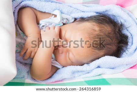 Child is lying in a crib in the daytime.