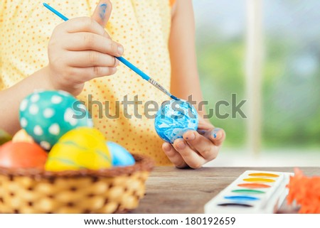Child is painting egg in blue color for Easter holiday, face is not visible - stock photo