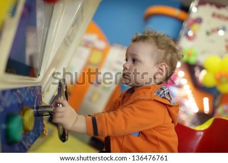 Child is playing with amusement machine at indoor playground - stock photo