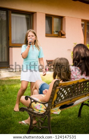 Child is singing with microphone in front of her mother and sister outdoor