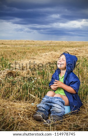 child is sitting in a field on the pot - stock photo