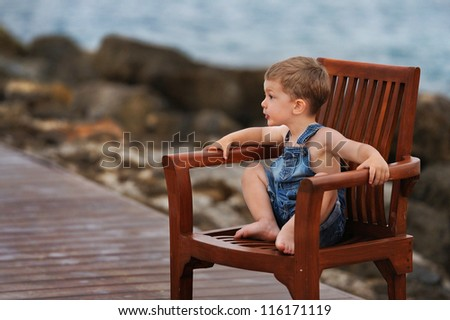 child is sitting in a wooden chair on the sea shore