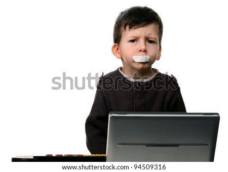 Child is sitting in front of a computer with tape on mouth - stock photo