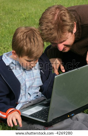Child is sitting with laptop in the park with his father