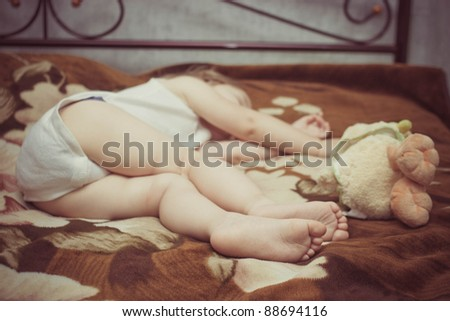 Child is sleeping with  toy duck. 4 feet. retro style