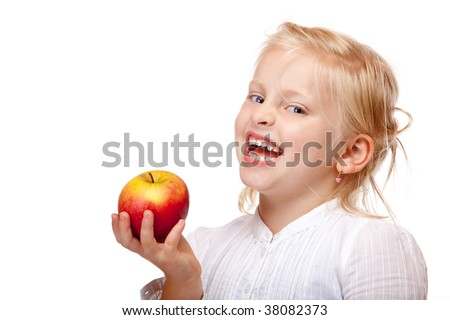 Child is smiling and holding a red apple. Isolated on white background - stock photo