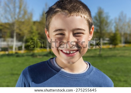 Child is smiling in a park looking at camera showing teeth - stock photo