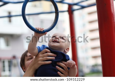 Child is snatching a gym ring at the outdoor playground - stock photo