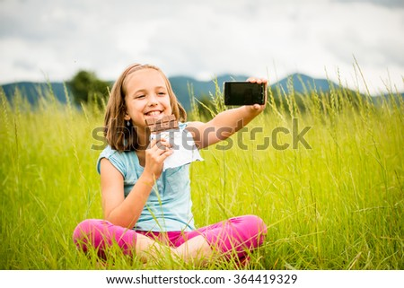 Child is taking photo with mobile phone camera while eating chocolate outdoor in nature - stock photo
