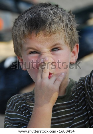 Child itching his nose after getting sand in it. - stock photo