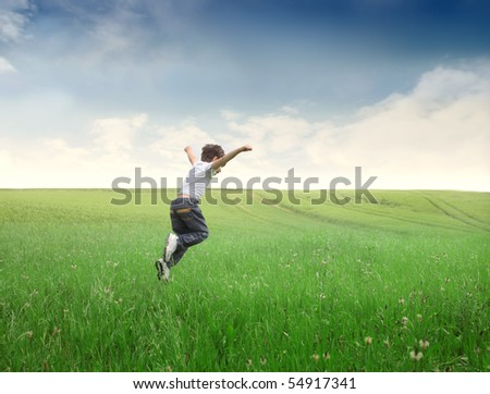 Child jumping on a green meadow - stock photo