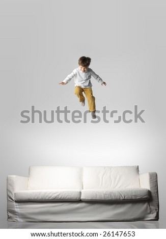child jumping on a sofa - stock photo