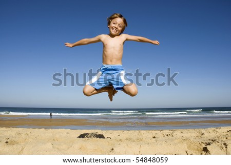 Child jumping on the beach - stock photo