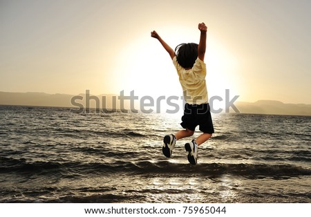 Child jumping over a sea in sunset - stock photo