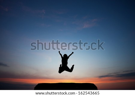 child jumps in sunset sky  - stock photo