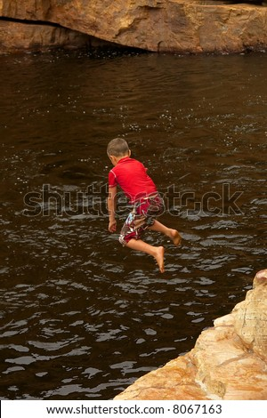 Child jumps into river from rock (slight motion blur). Shot in Cederberg Mountains, Western Cape, South Africa. - stock photo