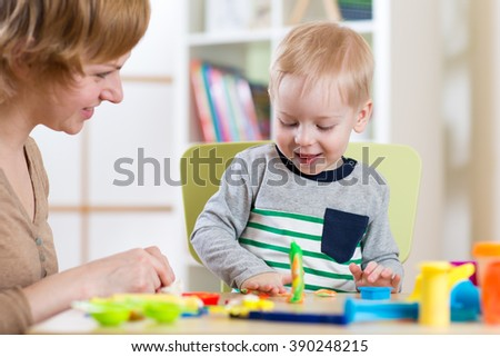 child kid boy and woman playing colorful clay toy at nursery or kindergarten - stock photo