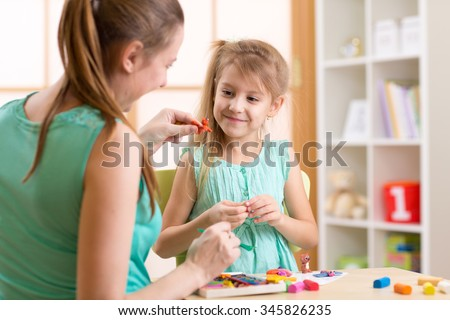 child kid girl and mother play colorful clay toys at nursery at home - stock photo