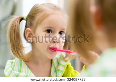 child kid girl brushes teeth looking at mirror in bathroom - stock photo