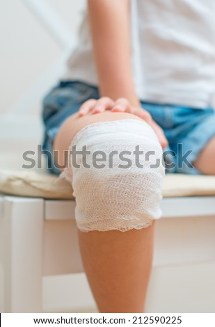 Child knee with adhesive and gauze bandage. - stock photo