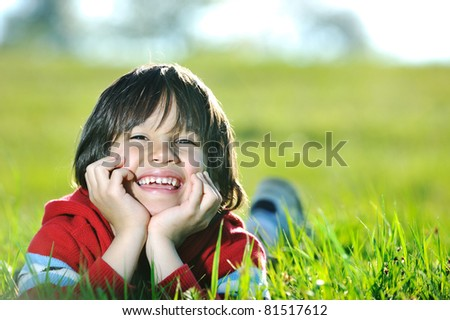 Child laying on meadow, boy at green grass in nature - stock photo