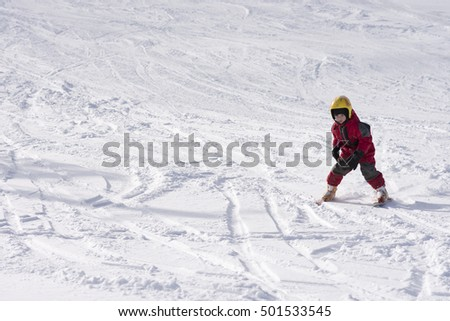 Child learning skiing on slope in winter