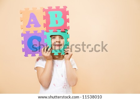 child learning the ABC's. The focus is on her eyes - stock photo