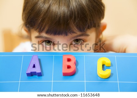 child learning the ABC's. The focus is on the letters - stock photo