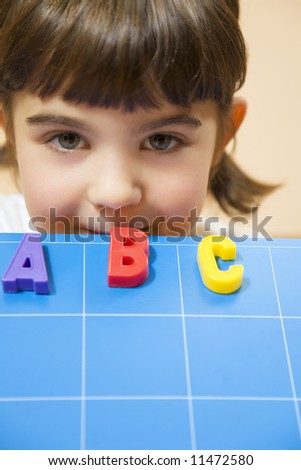 child learning the ABC's. The focus is on the mouth leaning on the blue board - stock photo