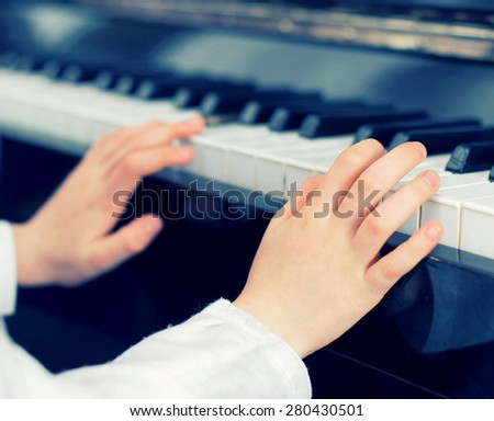 Child learning to play the piano. Vintage effect. - stock photo