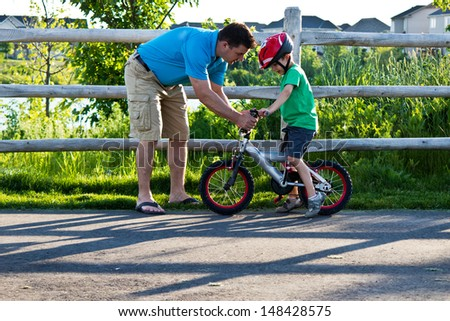 Child learning to ride a bicycle with father - stock photo