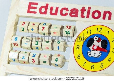 Child Learning Toy Abacus And Clock On whiteboard - stock photo
