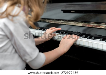 Child learns to play the piano. - stock photo