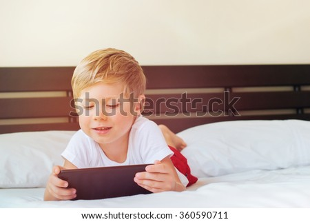 Child lies on bed and plays games on tablet. Inside. Toned image with sun light effect. Theme of modern technologies