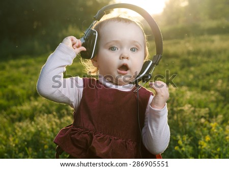 child listening to music on headphones - stock photo